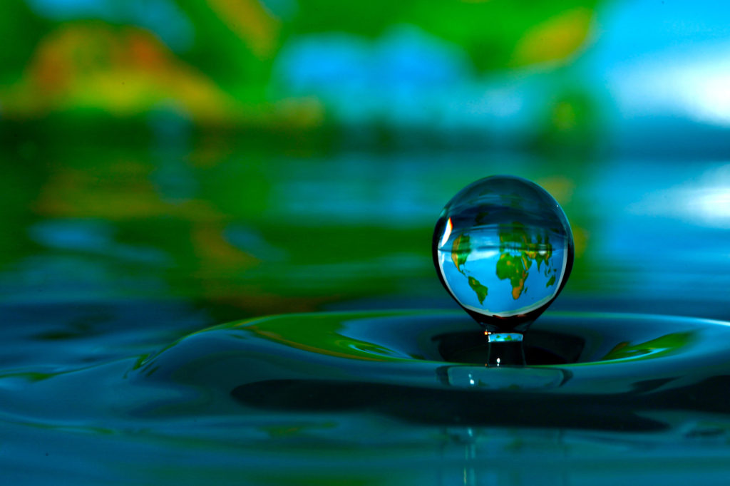 Using pictures in the background can lend a story to your water drop photo.