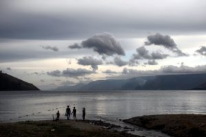 A family admire the view of the might lake Toba. Each silhouette is well defined.