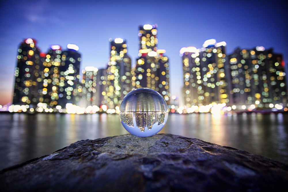 Lensballs are a photography producted used to create a refracted image. In this image a lensball refracts the image of Busan's marine city.