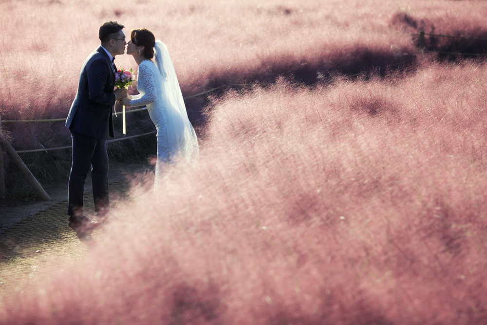 A South Korean couple pose for a photo in a muhly grass field. This is one of the best creative photos Simon Bond took in 2018.