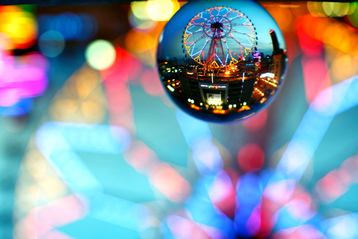 The bokeh background is a big part of lensball photography. Here a ferris wheel provides lines of light thoughout the photo, a ferris wheel like this makes an excellent main subject.